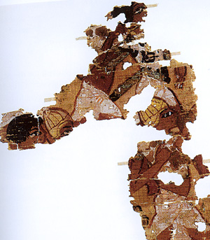 The British Museum has acquired some 40 fragments of a painted papyrus from Amarna (inv. no. EA 74100) with a unique representation of a battle. It was found in 1936 in a building which was probably a chapel dedicated to the cult of a king. The battle scene is preserved in two main areas. The first scene shows a group of Libyan archers attacking an Egyptian, while the second shows a group of running warriors, arranged in two overlapping registers. There is a very fragmentary third scene with similar figures. All the soldiers wear white kilts typical of Egyptian troops. Some wear helmet similar to Egyptian representation of gurpisu helmets worn by Asiatics. These helmets may actually have represented Achaean boar's tusk helmets. Some of the soldiers wear oxhide tunics which may have been lined with metal strips. This too is compatible with Achaean depictions of warriors.